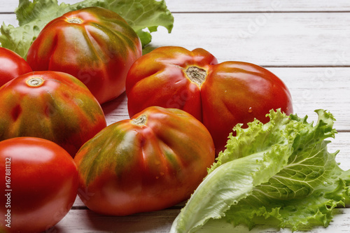 Red tomatoes and salad on white wooden board Canvas Print