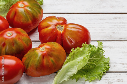 Fotografía  Red tomatoes and salad on white wooden board