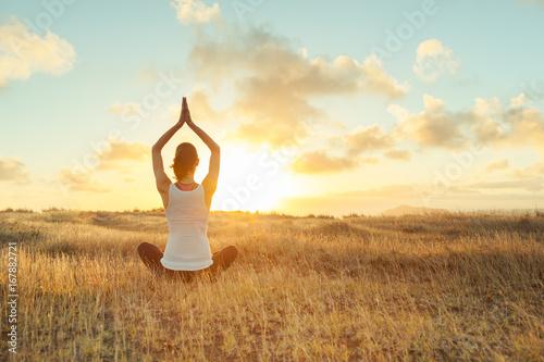 Obraz Woman doing yoga at sunset.  - fototapety do salonu