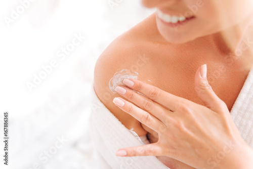 Fototapeta  Close up of female fingers that applying lotion