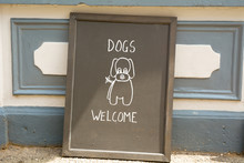 Dogs Welcome Chalkboard Sign Outside Cafe