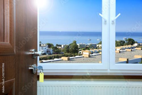 Widok z okna hotelu na dachy domów i morze. - 167895986