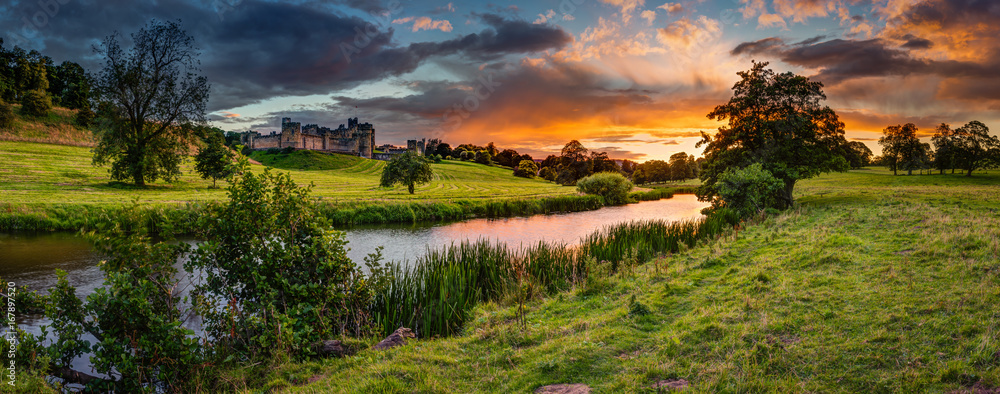 Fototapeta Panoramic Sunset over River Aln / The River Aln runs through Northumberland from Alnham to Alnmouth. Seen here in panorama below Alnwick Town and Castle on the skyline, as the sunsets