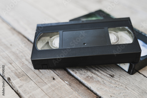 stack of VHS video tape cassette on white wooden table
