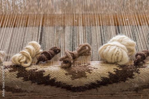 Fotografie, Obraz  Ukrainian wooden handloom creating a handwoven woollen fabric / carpet