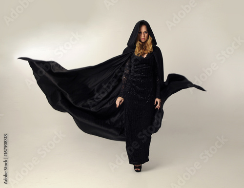 Fotografía  full length portrait of a blonde lady wearing black lace now and hooded cloak, standing pose isolated against creamy background