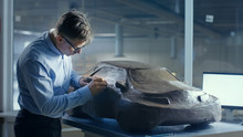 Grey Haired Automotive Designer Sculpts Futuristic  Car Model From Plasticine Clay With Wire. He Works In A Special Studio Located In A Large Car Factory.