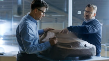 Two Male Automotive Designers Working On A Clay Model Of New Generation Electric Car Future Design. One Holds Tablet Computer For Graphic Design, Other Sculpts With Clay With Rake/Wire.