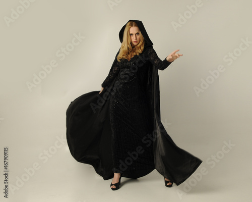 Photo  full length portrait of a blonde lady wearing black lace now and hooded cloak, standing pose isolated against creamy background