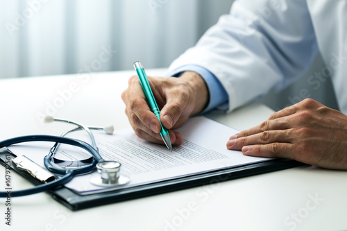 Fotografia  doctor writing documents at desk in clinics office