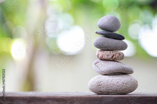 Montage in der Fensternische Zen Balance Stones stacked to pyramid in the soft nature green background.
