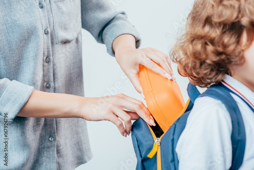 Fotografia  cropped shot of mother packing school lunch for son