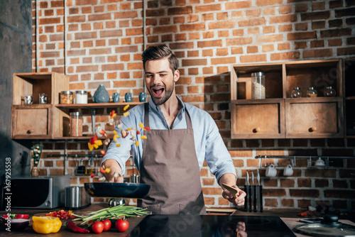 Fototapeta stylish young man with apron frying vegetables obraz