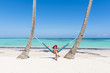 Juanillo Beach (playa Juanillo), Punta Cana, Dominican Republic. Woman relaxing on a hammock on the beach (MR).