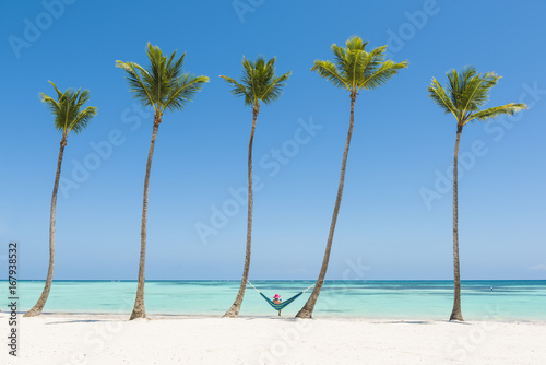 Deurstickers Strand Juanillo Beach (playa Juanillo), Punta Cana, Dominican Republic. Woman relaxing on a hammock on a palm-fringed beach (MR).