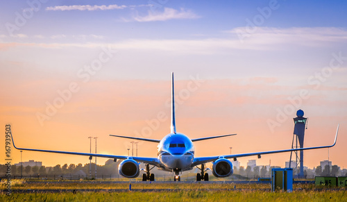 Fotografia  Front view of airplane at sunset, taken in Schiphol Airport, Netherlands