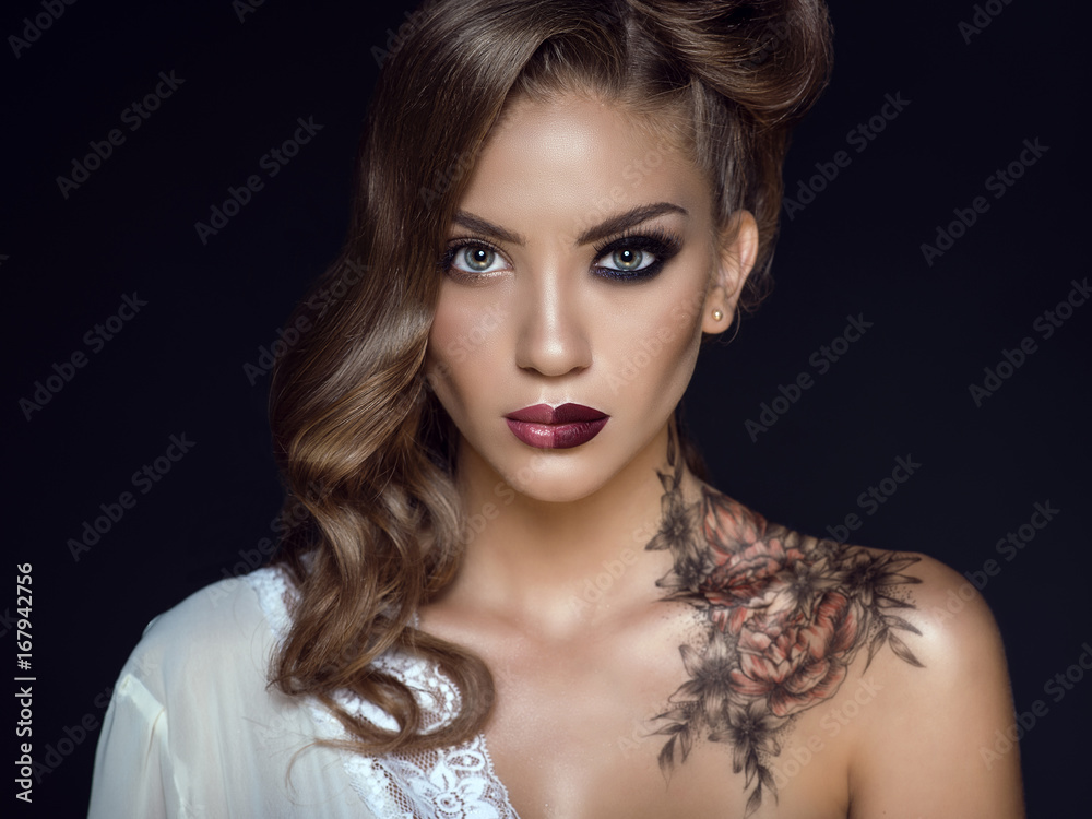 Fototapeta Close up portrait of beautiful model with artistic make up and hairstyle. Floral body art on her shoulder. Ideal woman concept. One half symbolizes a good housewife, another one – a passionate lover