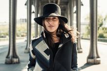Woman In A Hat Walking Among Metal Columns