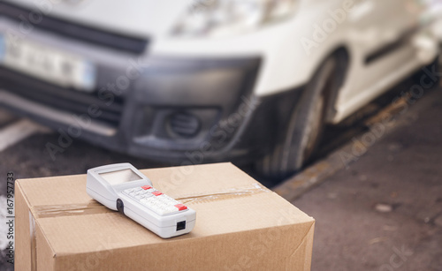 Parcel With Barcode Scanner And White Van - Buy this stock photo and