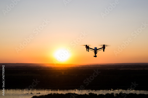 Staande foto Helicopter quadrocopter drone with remote control. Dark silhouette against colorfull sunset.