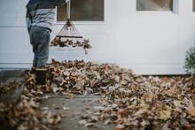 Boy Raking Leaves In Driveway