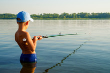 Boy Fishing Waist Deep In Water