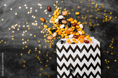 Fototapeta Halloween Party Trick of Treat Candy with candy flowing from party favor bag on dark wood background Flat lay, top view trendy holiday concept