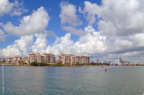 Fototapeta Luksusowe kondominium na wyspie, port Miami dźwigi załadunkowe i daleko Miami. sylwetka na tle nieba.