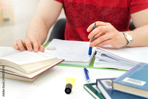 Young athletic man and student studying and writing notes in public or school library in college or university Canvas Print