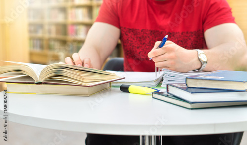 Photo Young athletic man and student studying and writing notes in public or school library in college or university