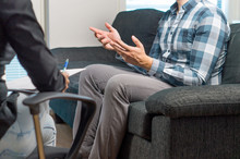 Man Talking And Waving Hands In Therapy Session With Psychiatrist, Psychologist, Counselor, Therapist Or Life Coach. Meeting With Professional Specialist With A Notepad. Male Patient Sitting On Couch.