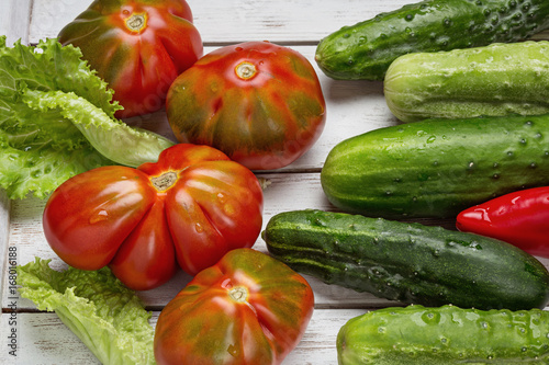 On a white wooden table, red tomatoes, cucumbers, lettuce and pepper Poster