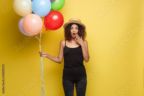Obraz na plátně  Celebration Concept - Close up Portrait happy young beautiful african woman in black t-shirt surprising with colorful party balloon