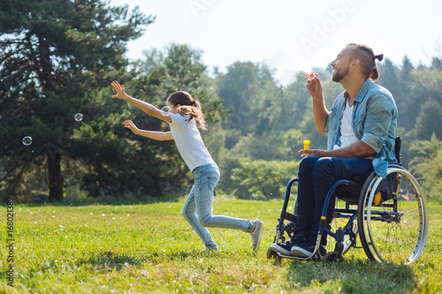Foto  Cheerful disabled father and daughter playing with soap bubbles