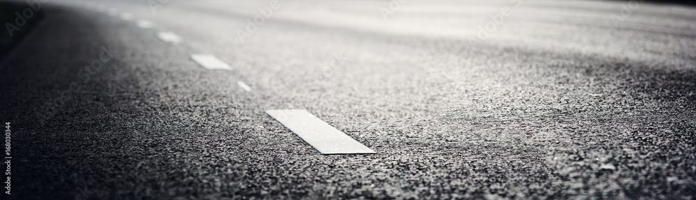 Fototapeta black asphalt road and white dividing lines