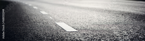 Leinwand Poster black asphalt road and white dividing lines