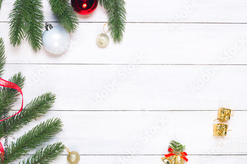 christmas and new year background fir leaves and decorations on white rustic wooden background with