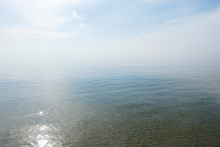 Calm Tranquil Blue Sea With No Waves And With Foggy Backgroudn