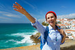 Woman with a backpack makes a welcome hand gesture on the ocean coast near Azenhas do Mar, Portugal