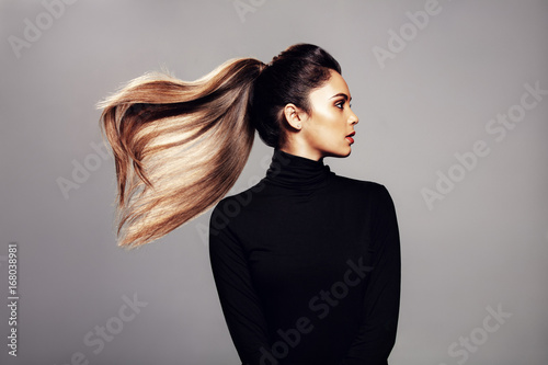 Foto op Plexiglas Kapsalon Stylish young woman with flying hair