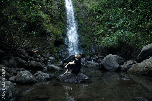 woman sitting in front of waterfall - 168046373