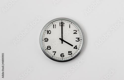 Zdjęcie XXL Biały zegar wisi na białej ścianie pokazującej czas 4:00