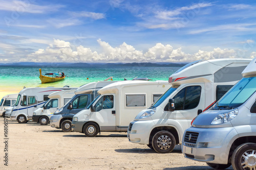Foto Close up motorhomes parked in a row on white sand beach and blue sky background