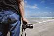 cropped image, a man standing with camera near the shore at sunny day