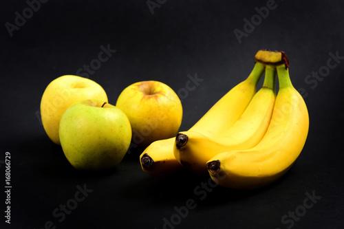 zolte-banany-i-jablka-na-czarnym-tle
