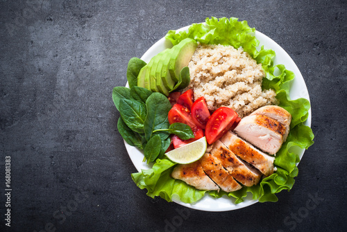 Photo  Fresh salad from quinoa, chicken breast, spinach, lettuce and tomatoes on black