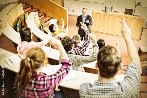Photo Students raising hands with teacher in lecture hall