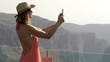 Young woman taking photo of canyon with cellphone standing on terrace