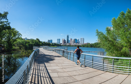 Poster Texas Panorama view Downtown Austin, Texas, US along Colorado River at daytime with cloud blue sky. View from Ann and Roy Butler Hike-and-Bike Trail and boardwalk at Lady Bird Lake, unidentified man running