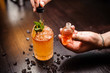 small skull-shaped bottle, summer cocktail and barmen hand